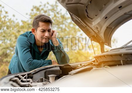 Man Open Car Hood For Repair As Maintenance Service. Man Trying To Check A Car Engine, Looking Insid