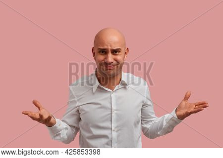 Why You Do This. Horizontal Shot Of Bald Guy With Bristle. With Puzzled Expression, Spreads Hands Wi