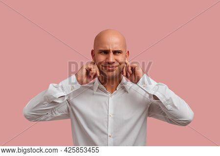 Can You Play Another Sound. Irritated Bald Guy With Bristle In White Shirt Plugs Ears, Dissatisfied