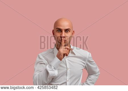Be Quiet Please. Pleasant Looking Bald Man With Bristle, Makes Hush Gesture, Looks At The Camera, As