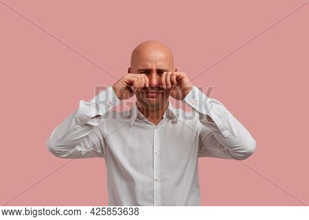 Horizontal Portrait Of Bald Man With Bristle In Desperation, Rubs Tears With Both Fists, By All Mean
