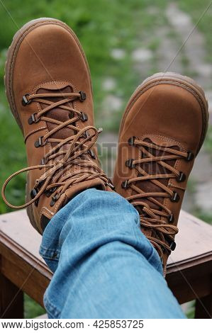 Brown Boots And Jeans On The Legs. Legs Are Crossed On The Stool.