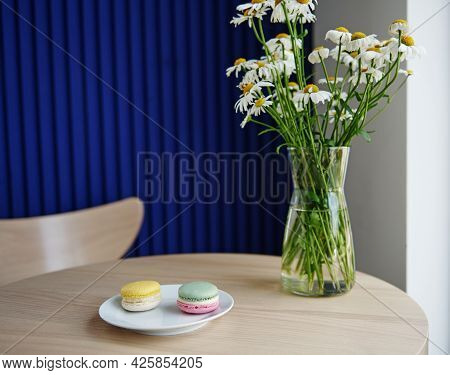 Served Table In Cafeteria With Macarons On A White Plate Near A Glass Vase With Chamomiles On It. St
