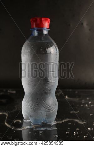 Cold Water In A Bottle On A Black Background. A Bottle Of Water Stands On A Black Background. Cool S