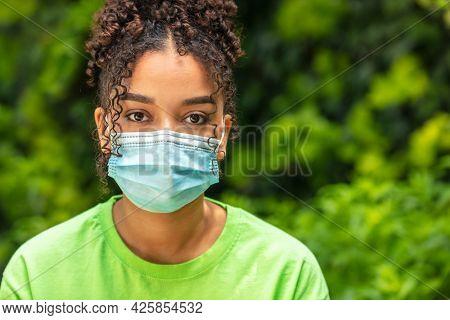 Girl teenager teen mixed race biracial African American female young woman wearing face mask in Coronavirus COVID-19 pandemic