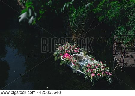 Wooden Boat Decorated With Flowers. Boat With Flowers On Lake. Beautiful View Of A Wooden Boat In A