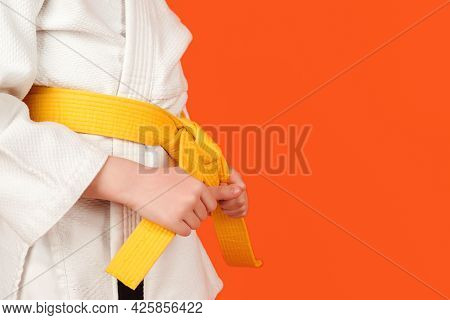 Kid In Karate Kimono Holding His Yellow Belt, Close Up. Boy Practicing Karate On Color Background, C