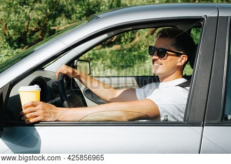Portrait Of Attractive Smiling Middle Aged Man Driving A Car And Holding Cup Of Coffee, Outside. Sid