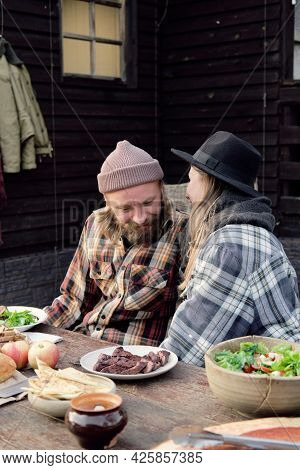 Young Couple Talking To Each Other While Sitting At The Table And Having Dinner During Picnic Outdoo