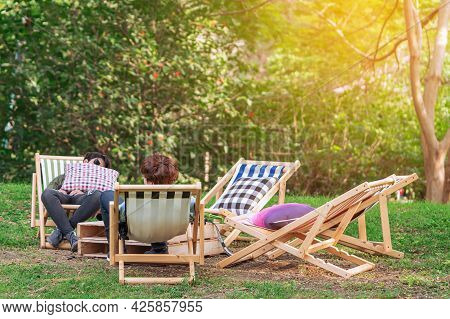 Back View Of Man And Friend Sit And Napping To Relax Together On Garden Chair In Garden. Summer Vaca