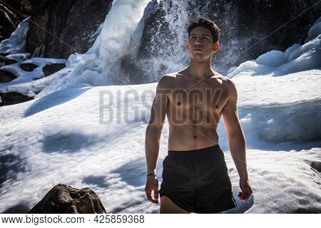 Shirtless Athletic Young Man Standing Near Snowy Waterfall