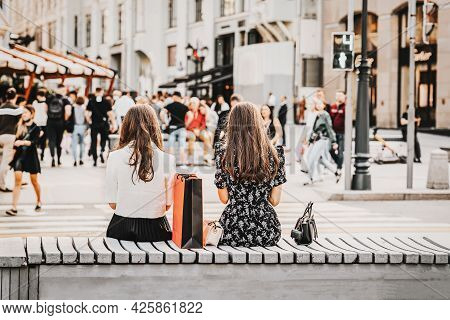 Two Girls Sitting On Bench, Summer Day, View From Behind, Blurred Pedestrians. Regular People Out In