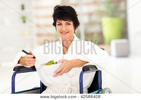 recovering middle aged woman eating salad on wheelchair