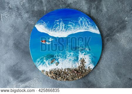 Resin Art Round Painting. Epoxy Art Composition With Blue Ocean Waves, Boat And Stone Beach. Flat La