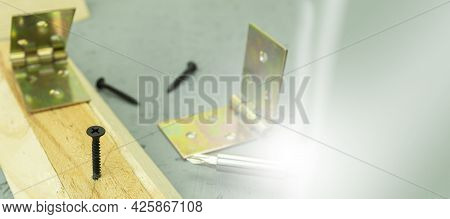 A Black Screw Is Screwed Into The Wooden Lath. Sun Glare On Tools And Building Materials. Background