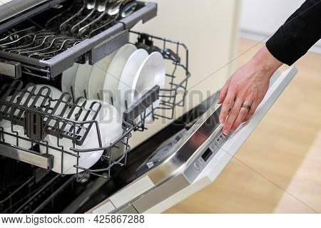 Woman Pressing Button On Dishwashing Machines Open Door, Selecting Cleaning Mode And Adjusting Water