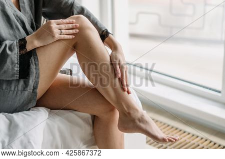 Cropped Shot Of Sensual Woman In Dressing Gown Touching Her Beautiful Legs With Smooth Epilated Skin