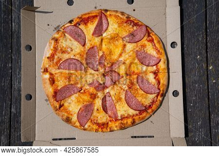 Pizza In A Cardboard Box Against A Dark Background. Space For Text. View From Above. Pizza Delivery.