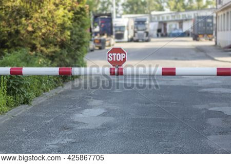 Barrier And Stop Sign On The Road. Entrance To Organization Gate, Checkpoint And Stop Sign