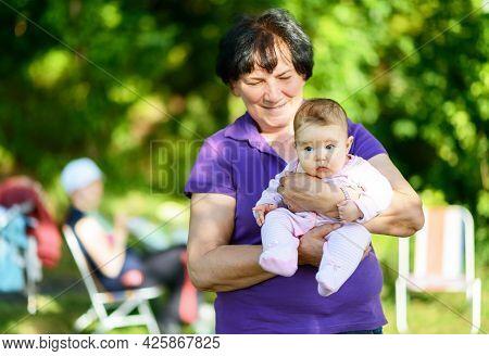 Newborn Baby Girl On Grandmother Hands, Portrait Of Infant Outdoor. Happy Senior Woman Holds Her Gra