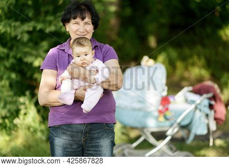 Newborn Baby Girl On Grandmother Hands, Portrait Of Infant Outdoor. Senior Woman Walks With Her Gran