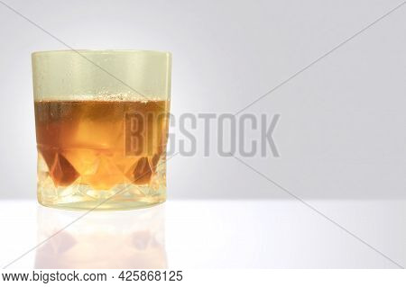 Misted Glass With Drops Of Water And Whiskey With Ice. Sweaty Glass Of Whiskey With Ice On Table Wit