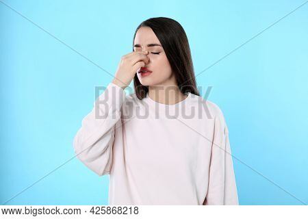 Young Woman Suffering From Runny Nose On Light Blue Background