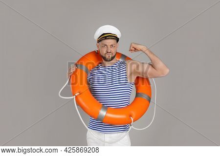 Strong Sailor With Orange Ring Buoy Showing Biceps On Grey Background