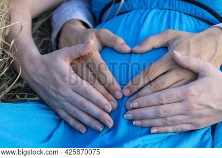 Pregnant Woman With Her Husband Hands On Her Stomach, Concept Of Waiting For A Child, Young Parents,