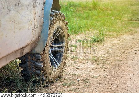 Wheel With Disc Dirty In A Swamp Off-road Tire Treads On A Rough Dusty Road With Grass Close-up.