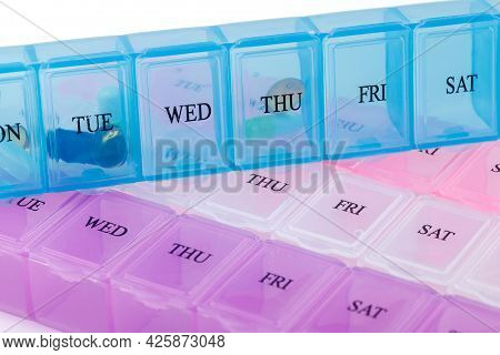 Blue Organizer With Medicines On Plastic Pill Organizers Isolated On White Background. Close Up Of A