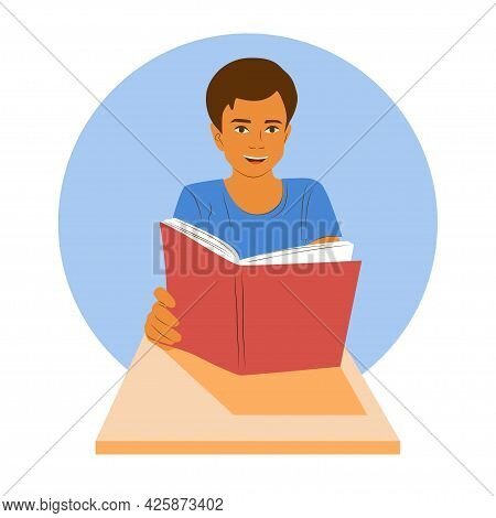 Young Smiling Boy Sits At A Desk And Holds A Book. School Boy Learning. Clever Happy Pupil On Lesson
