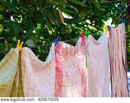 Towels With Clothespins Hanging On A Clothesline Outdoors. Summer Time.