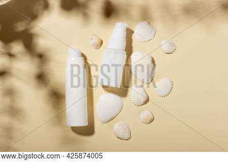 Set Of White Cosmetic Bottles And Jars With Seashells On A Beige Background With Hard Shadows. The C