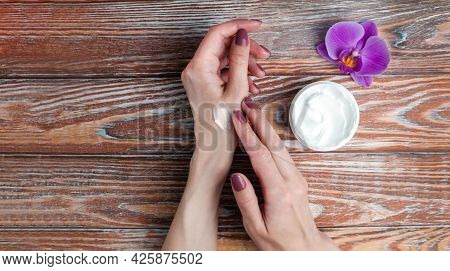 Woman Smears Moisturizing Cream On Hands On Wooden Background. Hand Skin Care Concept. Flatlay Compo