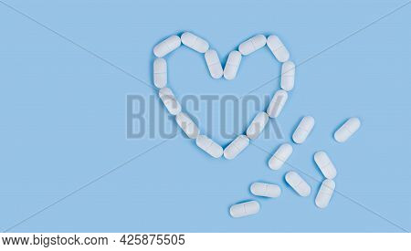 White Pills In Shape Of Heart On The Blue Background. Medicine Concept. Flatlay. Top View. Place For