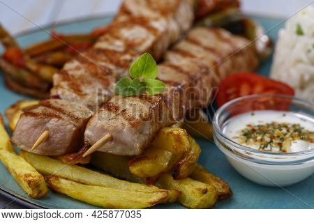Greek Souvlaki Skewers With French Fries On A Blue Plate
