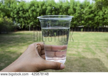Female Holding Glass Of Clean Filtered Water In Transparent Disposable Glass At Home Garden With Bac