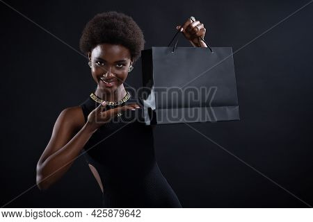 African American Black Woman With Afro Hairstyle Pointing With Hand Black Shopping Bag. Sale And Bla