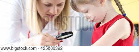 Doctor Examining Pigmented Nevus On Little Girls Hand With Magnifying Glass