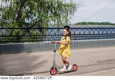 A Charming Girl Rides A Scooter Along The River Bank With A Wrought-iron Fence On A Sunny Summer Day
