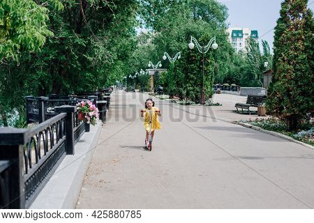 A Girl Rides A Scooter In A City Landscape With Street Lights, A Wrought-iron Fence And Trees