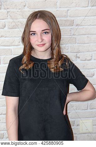 Girl With Lush Hairstyle Posing On Brick Wall Background. Portrait Of Girl In Black Dress. Hairstyle