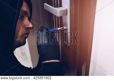 Close Up Of A Burglar With Gloves Picking A Lock.