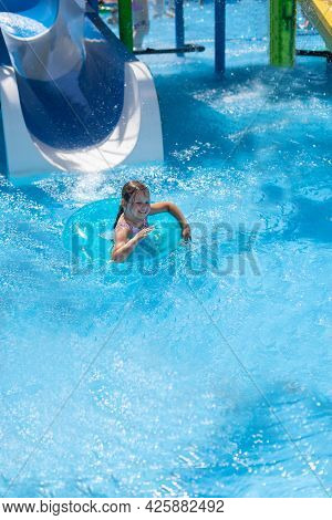 A Girl In An Inflatable Circle Slides Down A Water Slide Into The Pool And Sends Splashes Of Water I