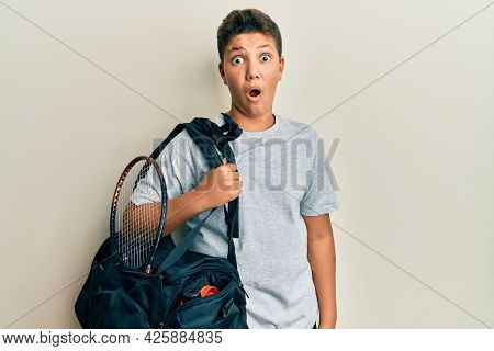 Teenager hispanic boy holding sport bag scared and amazed with open mouth for surprise, disbelief face