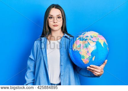 Young hispanic girl holding world ball thinking attitude and sober expression looking self confident