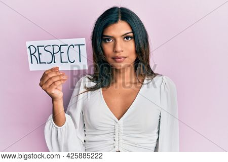 Young latin transsexual transgender woman holding respect message paper thinking attitude and sober expression looking self confident