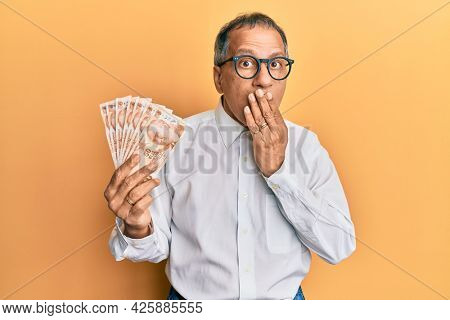 Middle age indian man holding 50 turkish lira banknotes covering mouth with hand, shocked and afraid for mistake. surprised expression