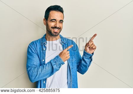 Young hispanic man pointing with fingers to himself winking looking at the camera with sexy expression, cheerful and happy face.